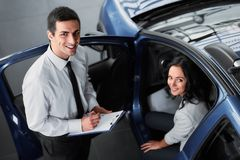 Car sales. Attractive women at car salon with consultant choosing a car royalty free stock image