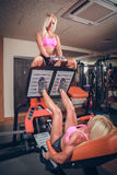 Attractive women in gym on workout machine Stock Photo