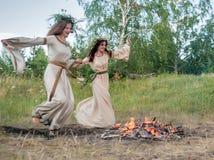 Attractive women jumping through fire Stock Photos