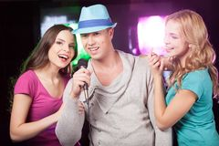 Attractive women and man singing karaoke. Beautiful trio standing at bar and singing in mic Royalty Free Stock Images