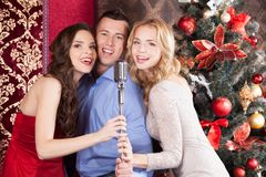 Attractive women and man singing karaoke. Beautiful trio standing at home and singing in mic Stock Photos