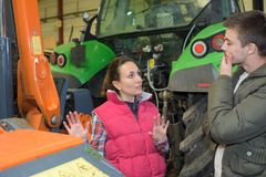 Attractive woman selling brand new tractor to beginner farmer. Attractive women selling brand new tractor to beginner farmer selling stock images