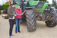 Attractive woman selling brand new tractor to beginner farmer Stock Images