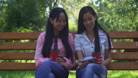 Attractive women spend free time at the open air. Two asian friends drinking coffee to go and watching funny video on smartphone. Laughing businesswoman or stock footage