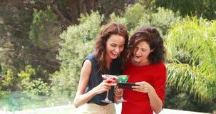 Attractive women taking a selfie. Poolside stock video
