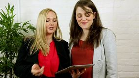 Attractive women using and demonstrating tablet app stock footage