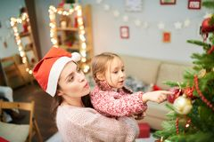 Loving Family Decorating Christmas Tree. Attractive women wearing Santa hat holding her little daughter on arms while decorating Christmas tree together Royalty Free Stock Images