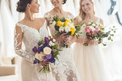 Attractive women in wedding dresses laughing. In wedding salon stock image