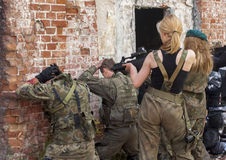 Attractive womens in military uniform, holding gun and aim to sh stock photos