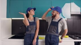 Happy satisfied their work man and woman of the cleaning service giving high five in the blue-black cuisine