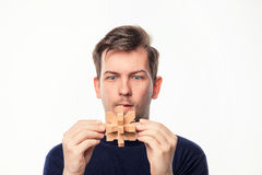 Attractive 25 year old business man looking confused at wooden puzzle. Stock Image