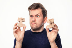 Attractive 25 year old business man looking confused at wooden puzzle. Royalty Free Stock Images