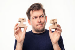 Attractive 25 year old business man looking confused at wooden puzzle. Stock Photos