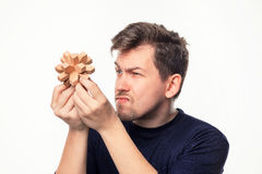 Attractive 25 year old business man looking confused at wooden puzzle. Royalty Free Stock Photos
