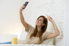 Attractive 30 years old woman playing on home sofa couch taking selfie portrait with mobile phone Royalty Free Stock Photo