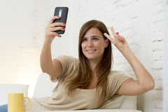 Attractive 30 years old woman playing on home sofa couch taking selfie portrait with mobile phone Stock Photos