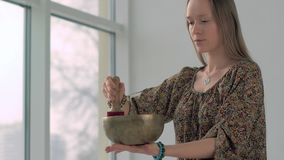 Attractive yoga girl playing the singing bowl while practicing yoga stock video