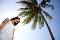 Attractive yougn woman under palm tree. Pretty girl with white causal dress smiling under palm tree Stock Photography