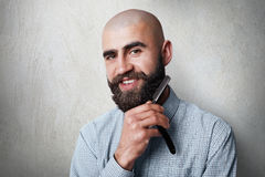 Attractive yound balded barber with thick black beard and mustache smiling while holding straight razor on his beard. A young hair Stock Photos