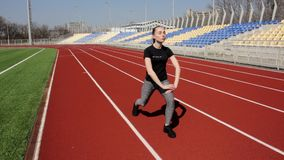 Attractive young active fit girl workout doing leg upper body stretch exercise to warm up tone muscles at big stadium stock footage
