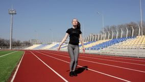 Attractive young active fit girl workout upper body leg stretch exercise jumping to warm up tone muscles at big stadium. Attractive young active fit girl workout stock video