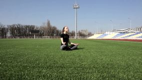 Attractive young active fit woman does yoga on huge stadium green grass meditating calmly enjoying warm sunny spring day stock footage