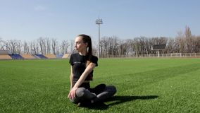 Attractive young active fit woman does yoga stretch pose on huge stadium green grass meditating calmly on warm sunny day stock video