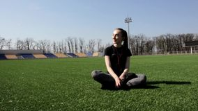 Attractive young active fit woman sitting on huge stadium green grass laughing smiling enjoying warm sunny spring day stock video footage