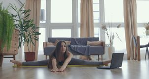 Attractive young active woman taking online stretching yoga classes at home, watching tutorial on laptop. Healthy life
