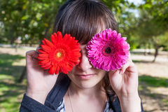 Attractive young adult covering her eyes with red and violet ger Royalty Free Stock Photography