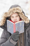Attractive young adult man in winter clothes reading a book Stock Image