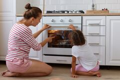 Attractive young adult mother wearing striped shirt and shorts sitting on floor near gas-stove with her daughter, female pointing