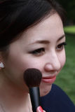 Attractive young adult woman applying blusher Stock Photo