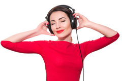 Attractive young adult woman in red clothes listening to the mus Stock Photography