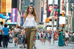 Attractive young adult woman walking around crownd on New York City street and carrying a bag wearing white top Stock Photos