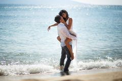 Two married young adults, men holding his wife passionately, sitting in the water, isolated on a seascape background. royalty free stock photography