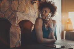 Black girl phoning while sitting in dark meeting room. Attractive young African American female is sitting on verandah of summer house on sunny day and talking royalty free stock photos