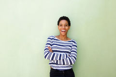 Attractive young african american woman smiling against green wall Stock Photo