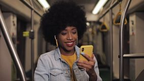 Attractive young african american woman using smartphone riding at public transport. She watching video and smiling stock video footage