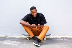 Attractive young african man sitting with skateboard and using smart phone Royalty Free Stock Photos