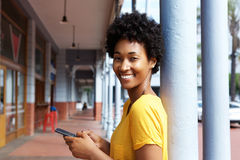 Attractive young african woman holding a mobile phone Stock Photos
