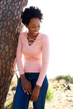 Attractive young african woman leaning to a tree Royalty Free Stock Photography