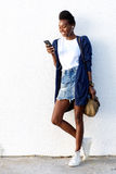 Attractive young african woman using smart phone Royalty Free Stock Photos