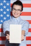 Attractive young American businesswoman is expressing patriotism. I like studying in United States of America. Cheerful woman is holding a book and showing it to Stock Photo
