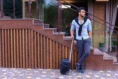 Attractive young Arabic man standing with suitcase in hand and p Royalty Free Stock Photography