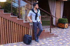 Attractive young Arabic man standing with suitcase in hand and p Stock Photo