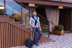 Attractive young Arabic man standing with suitcase in hand and p Stock Photography