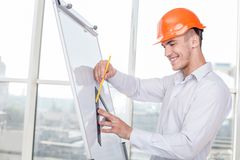Attractive young architect is working on plan of Stock Images