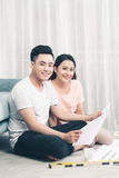 Attractive young asian adult couple looking at house plans. Royalty Free Stock Image