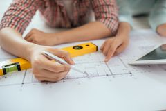 Attractive young asian adult couple looking at house plans. Attractive young asian adult couple looking at house plans Stock Image